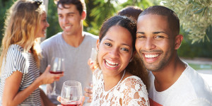 Couple With Friends Drinking Wine And Relaxing Outdoors